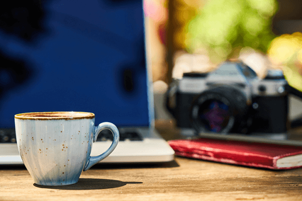 Zestaw przedmiotów przydatnych do nauki: Laptop, książka, aparat, filiżanka.