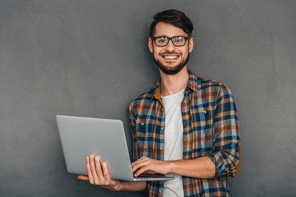 Uśmiechnięty młody mężczyzna z laptopem.