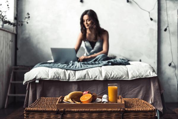 Widok na młodą kobietę, która siedzi na łóżku i pracuje na laptopie. Na pierwszym planie taca z posiłkiem.