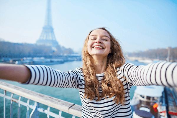 Dziewczyna w pasiastej bluzce robi selfie na tle wieży Eiffle'a.