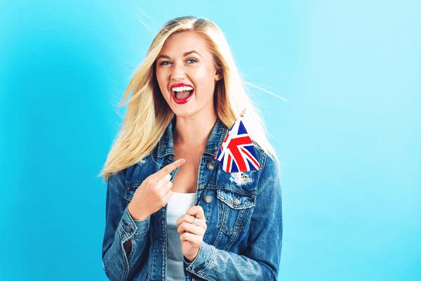 Młoda uśmiechnięta dziewczyna trzymająca flagę Wielkiej Brytanii.