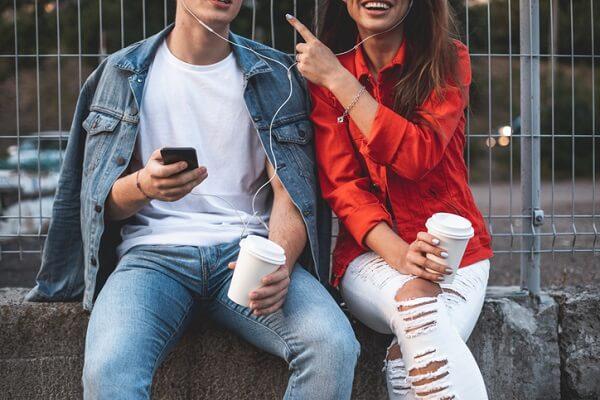 Para młodych ludzi pije kawę i wspólnie słucha audiobooka.
