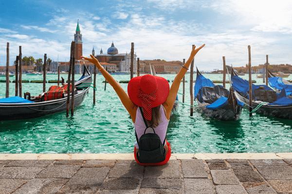 Kobieta w kapeluszu siedzi na przystani. W tle widok na Wenecję.