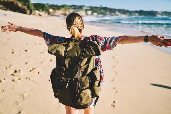 Kobieta z plecakiem na plaży.