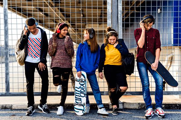 Piątka młodych skaterów słuchająca nagrań na słuchawkach.