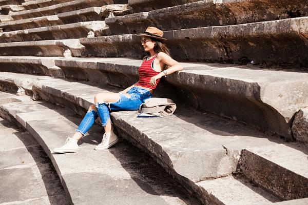 Dziewczyna siedząca na ruinach rzymskiego amfiteatru.