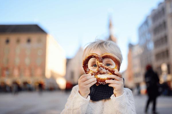 Chłopiec z preclem na rynku niemieckiego miasta.