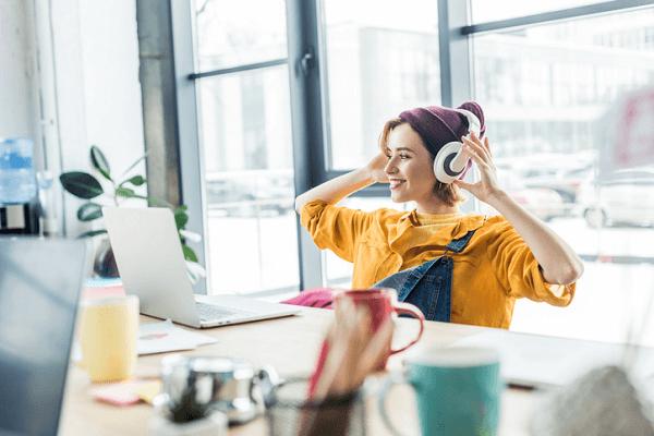 Wesoła, modnie ubrana nastolatka siedzi przed komputerem i zakładka słuchawki na uszy.