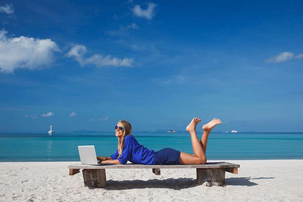 Dziewczyna wypoczywająca na plaży z laptopem. W tle spokojne morze.