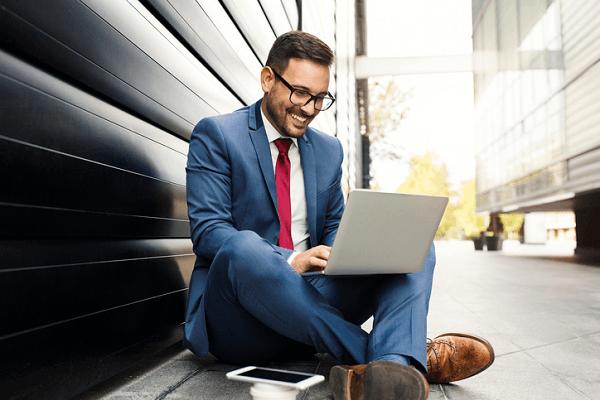 Zrelaksowany biznesmen pracuje na laptopie siedząc po turecku na ulicy.