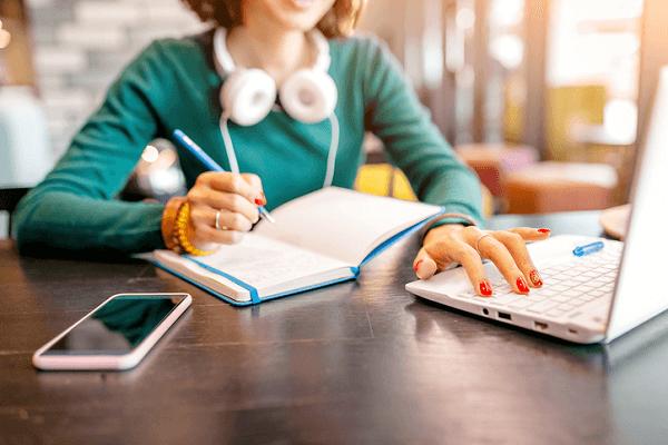 Na zdjęciu widzimy uczącą się przed komputerem kobietę, która robi notatki w zeszycie. Na szyi ma przewieszone słuchawki. Na jej biurku leży smartfon.