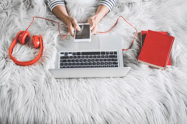 Osoba podczas nauki korzysta z telefonu, laptopa, słuchawek i książek.