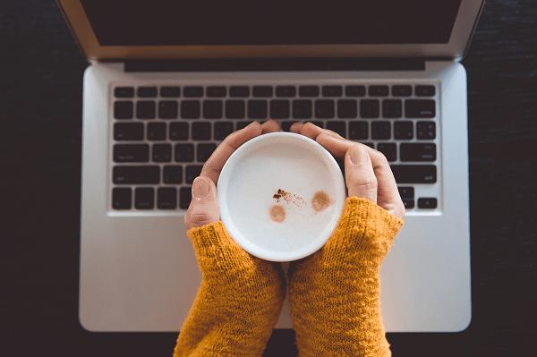 Widok z góry na dłonie trzymające filiżankę z kawą ponad klawiaturą laptopa.
