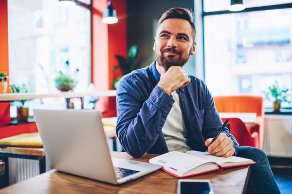 Mężczyzna w nowoczesnym biurze pracuje z laptopem i tradycyjnym kalendarzem.