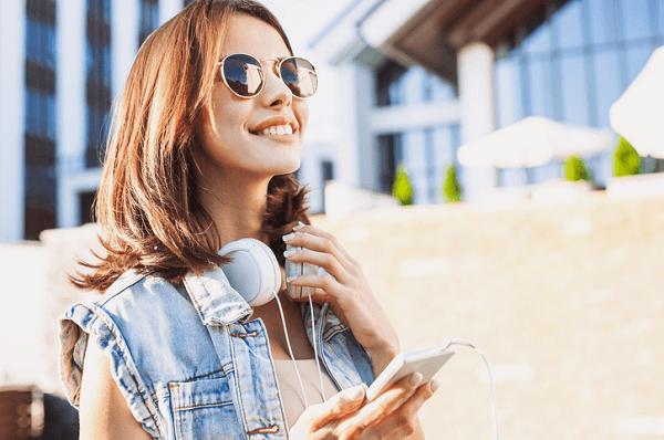 Dziewczyna w okularach słonecznych i ze słuchawkami przewieszonymi na szyi, trzyma telefon i patrzy w dal. Uśmiecha się radośnie.