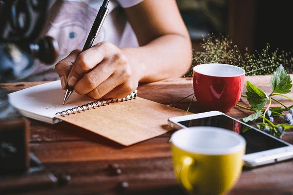 Na zdjęciu widoczna damska ręka notująca coś w zeszycie. Obok stoją kolorowe filiżanki, telefon i kwiaty.