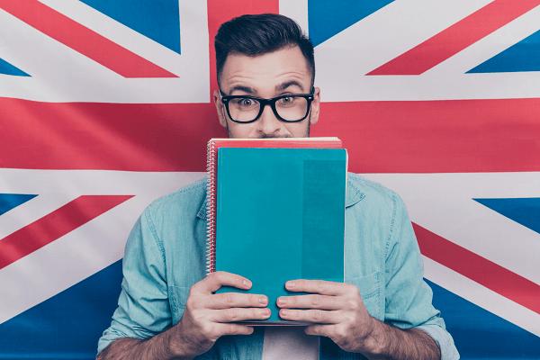 Mężczyzna w okularach zasłania usta zeszytem. W tle flaga brytyjska.