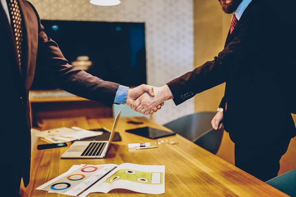 Mężczyźni podczas spotkania biznesowego podają sobie ręce ponad stołem.