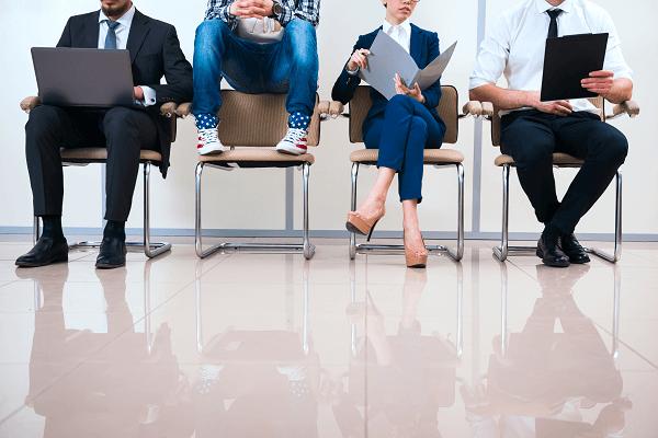 Czworo osób oczekuje na rozmowę kwalifikacyjną. Troje z nich jest elegancko ubranych, przeglądają w dokumenty. Jeden mężczyzna ubrany jest w nieoficjalnym stylu, nosi trampki we wzór amerykańskiej flagi. Siedzi na oparciu krzesła i bawi się telefonem.