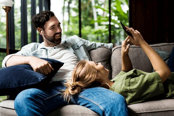 Para uczy się wspólnie na kanapie w domu. Mężczyzna ma założone słuchawki, kobieta korzysta ze smartfona.